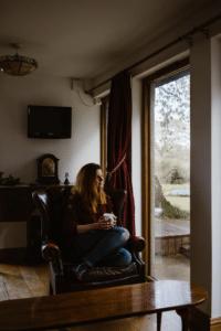 Frau sitzt auf einem gemütlichen Sofa zu Hause